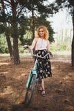 一条美丽的裙子的一个女孩有红色头发的在她的自行车附近支持森林 夏天步行在森林里 免版税库存图片