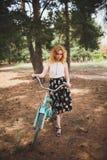 一条美丽的裙子的一个女孩有红色头发的在她的自行车附近支持森林 夏天步行在森林里 库存图片