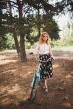 一条美丽的裙子的一个女孩有红色头发的在她的自行车附近支持森林 夏天步行在森林里 库存照片