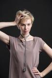 一条美丽的年轻白肤金发的妇女佩带的新潮论点项链的画象 免版税库存图片
