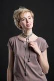 一条美丽的年轻白肤金发的妇女佩带的新潮论点项链的画象 库存图片