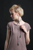 一条美丽的年轻白肤金发的妇女佩带的新潮论点项链的画象 免版税库存照片