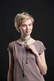 一条美丽的年轻白肤金发的妇女佩带的新潮论点项链的画象 免版税图库摄影