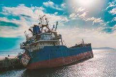 一条老海难小船的关闭放弃了在海滩的立场或遭受了海难在离海岸的附近  图库摄影