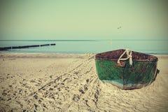 一条老生锈的钢小船的减速火箭的被过滤的图片在海滩的 免版税库存照片