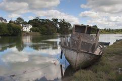 一条老被中断的小船的废墟在河的岸的 免版税库存图片