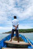 一条蓝色小船的人 免版税库存图片