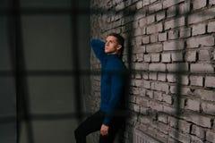 一条蓝色毛线衣和黑裤子的,在一个石墙附近的赤足立场白可爱的人,关在监牢里,囚犯 库存图片
