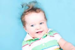 一条蓝色毯子的逗人喜爱的卷曲婴孩 免版税库存照片