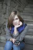 一条蓝色围巾的微笑的女孩坐石台阶户外 免版税图库摄影