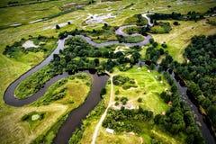 一条蜿蜒的河的谷的顶视图在绿色中的 免版税库存图片