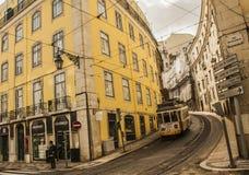 一条街道在里斯本,葡萄牙 电车和一个黄色大厦 图库摄影
