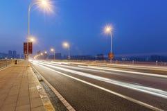 一条街道的夜街道在有轻的足迹的上海 免版税库存图片
