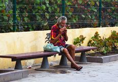 一条街道长凳的一个无家可归的叫化子在Playa捉住休息的美洲日报,当兴旺的世界通过他时 免版税库存图片
