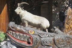一条被充塞的山羊和被雕刻的木鳄鱼的雕刻的构成在塔的脚在山大阿安,索契 库存照片