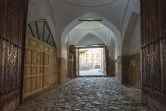 一条被成拱形的通道的被雕刻的木门在Khiva,乌兹别克斯坦 免版税库存图片