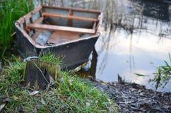 一条被毁坏的小船在河岸停泊了由铁链子 免版税库存图片