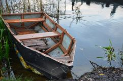 一条被毁坏的小船在河岸停泊了由铁链子 库存照片