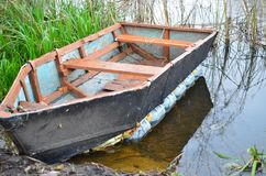 一条被毁坏的小船在河岸停泊了由铁链子 库存图片