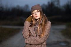 一条被编织的帽子和围巾的女孩在晚上在秋天结冰在自然 免版税库存照片