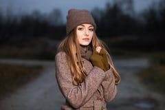一条被编织的帽子和围巾的女孩在晚上在秋天结冰在自然 免版税图库摄影