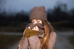一条被编织的帽子和围巾的女孩在晚上在秋天结冰在自然 免版税库存图片
