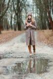 一条被编织的帽子和围巾的女孩在秋天的一个水坑在自然 免版税库存照片