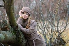 一条被编织的帽子和围巾的女孩在秋天的一棵下落的树在自然 免版税库存图片