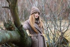 一条被编织的帽子和围巾的女孩在秋天的一棵下落的树在自然 图库摄影