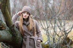 一条被编织的帽子和围巾的女孩在秋天的一棵下落的树在自然 库存图片