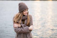 一条被编织的盖帽和围巾的女孩在自然的秋天 冷 库存图片