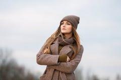 一条被编织的盖帽和围巾的女孩在自然的秋天 冷 免版税库存图片
