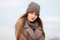 一条被编织的盖帽和围巾的女孩在自然的秋天 冷 库存照片