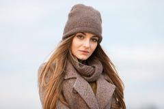 一条被编织的盖帽和围巾的女孩在自然的秋天 冷 图库摄影