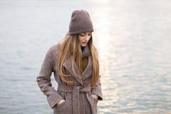 一条被编织的盖帽和围巾的女孩在自然的秋天 冷 免版税库存照片