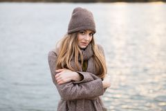一条被编织的盖帽和围巾的女孩在自然的秋天 冷 免版税图库摄影