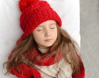 一条被编织的红色盖帽和大舒适围巾的睡觉在一张白色床上和享受甜胜利的一个美丽的小女孩的照片 库存图片