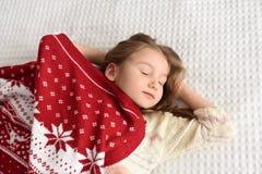 一条被编织的红色盖帽和大舒适围巾的睡觉在一张白色床上和享受甜胜利的一个美丽的小女孩的照片 库存照片
