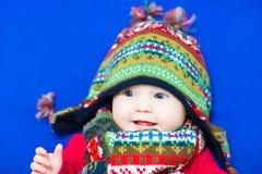 一条被编织的五颜六色的帽子和围巾的婴孩在一条蓝色毯子 免版税库存图片