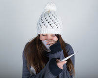 一条被编织的帽子和围巾的少妇,握在温度计的手 她似乎病 库存照片