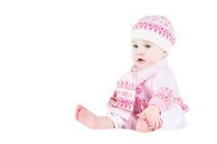 一条被编织的毛线衣、帽子和围巾的美丽的女婴 库存图片