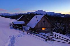 一条被践踏的道路导致雪的木房子在美丽的积雪覆盖的山背景  库存图片