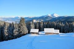 一条被践踏的道路导致雪的木房子在美丽的雪加盖的山背景  库存照片