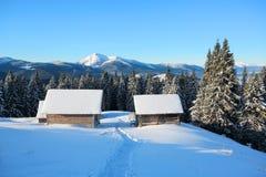 一条被践踏的道路导致雪的木房子在美丽的雪加盖的山背景  免版税库存照片