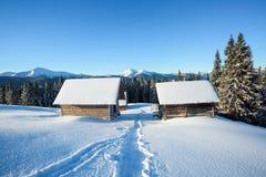 一条被践踏的道路导致雪的木房子在美丽的雪加盖的山背景  免版税库存图片