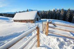 一条被践踏的道路导致雪的木房子在美丽的雪加盖的山背景  图库摄影