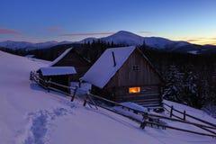 一条被践踏的道路导致雪的木房子 免版税库存照片