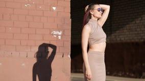 一条裙子和太阳镜的年轻美女反对砖墙背景 风振翼头发 股票视频