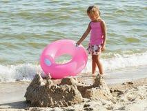 一条裙子的女孩有的孩子的lifebuoy在海滩 图库摄影