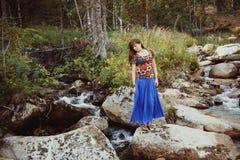 一条裙子的妇女在石头 免版税库存图片